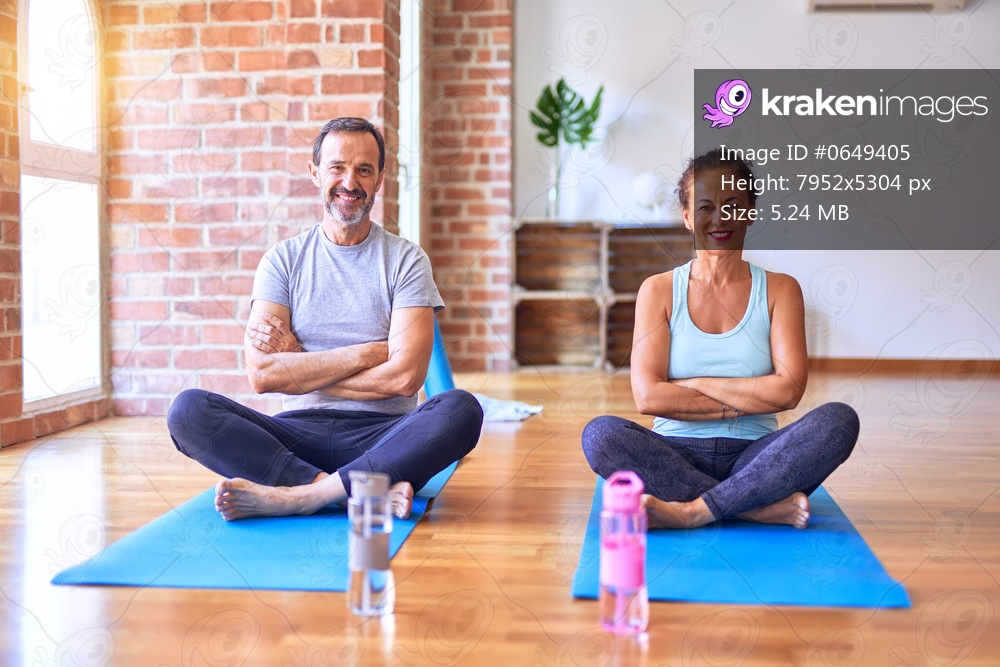 Middle age sporty couple sitting on mat doing stretching yoga exercise at gym happy face smiling with crossed arms looking at the camera. Positive person.