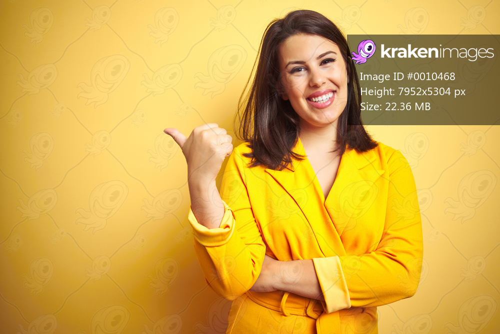 Young beautiful brunette woman wearing elegant dress over yellow isolated background smiling with happy face looking and pointing to the side with thumb up.