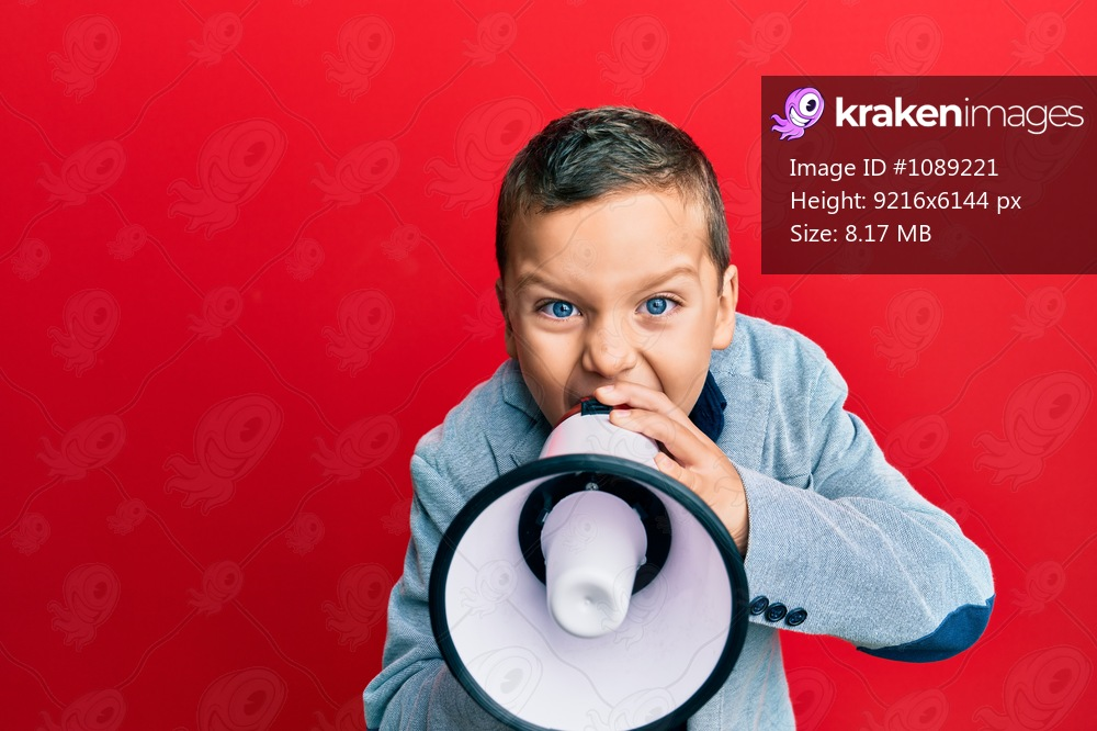 Adorable caucasian boy screaming using megaphone over isolated red background.