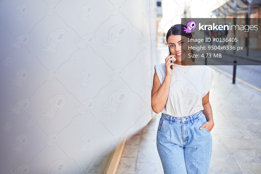 Beautiful young woman wearing fashionable clothes walking down the street and using smartphone telephone