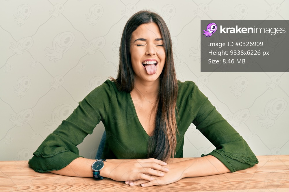Young brunette woman wearing casual clothes sitting on the table sticking tongue out happy with funny expression. emotion concept.