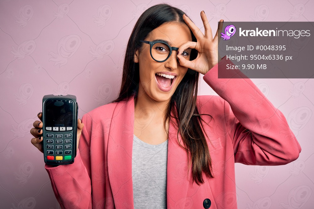 Young beautiful brunette woman holding dataphone paying with credit card to finance with happy face smiling doing ok sign with hand on eye looking through fingers
