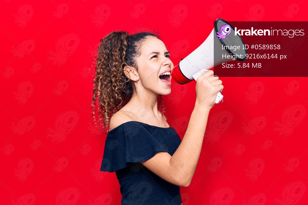 Adorable latin teenager girl with angry expression. Screaming loud using megaphone standing over isolated red background