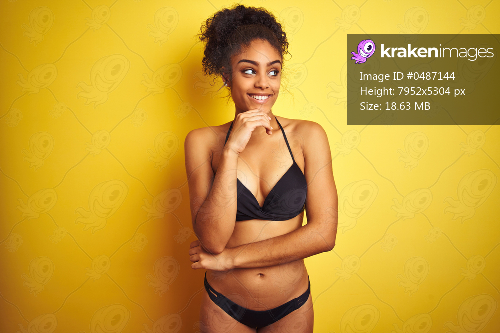 African american woman on vacation wearing bikini standing over isolated yellow background with hand on chin thinking about question, pensive expression. Smiling and thoughtful face. Doubt concept.
