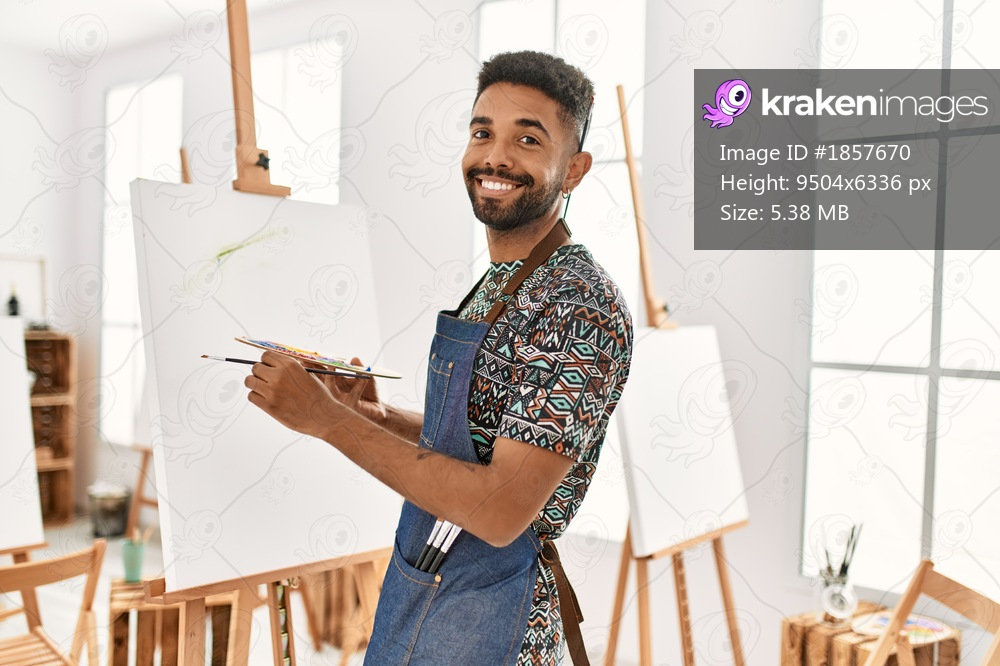 Young african american artist man smiling happy painting at art studio.