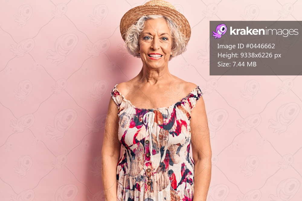 Senior grey-haired woman wearing summer hat with a happy and cool smile on face. lucky person.