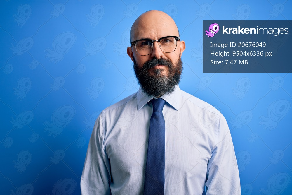 Handsome business bald man with beard wearing elegant tie and glasses over blue background Relaxed with serious expression on face. Simple and natural looking at the camera.