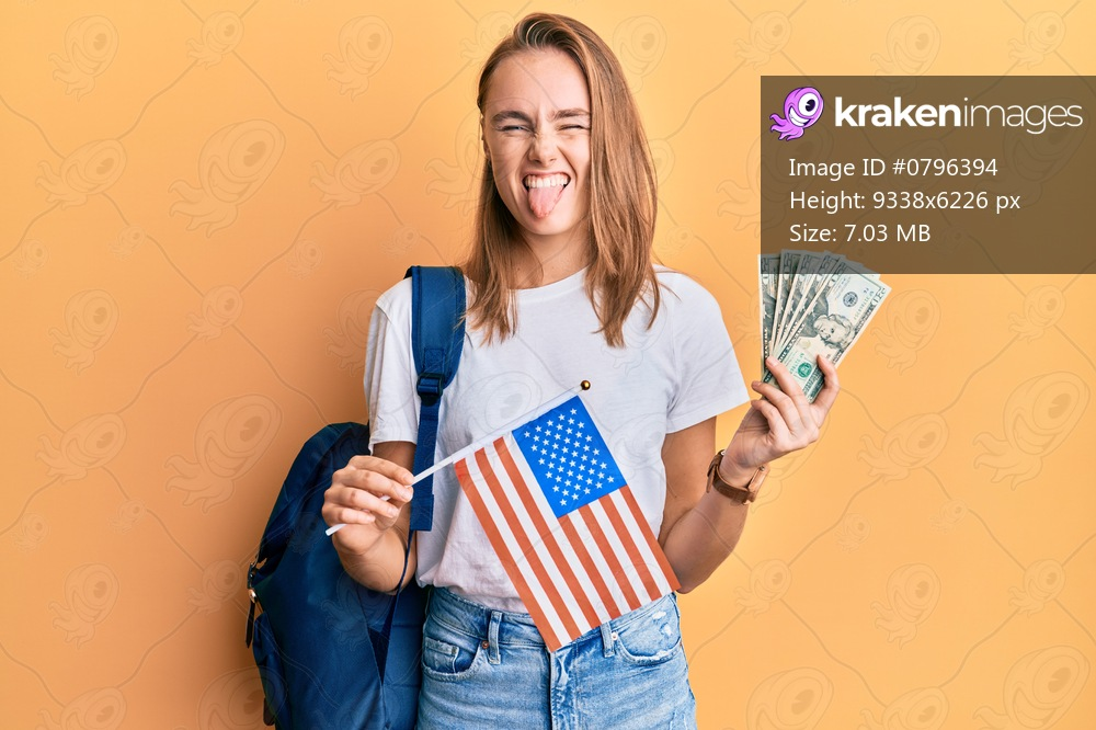 Beautiful blonde woman exchange student holding usa flag and dollars banknotes sticking tongue out happy with funny expression.