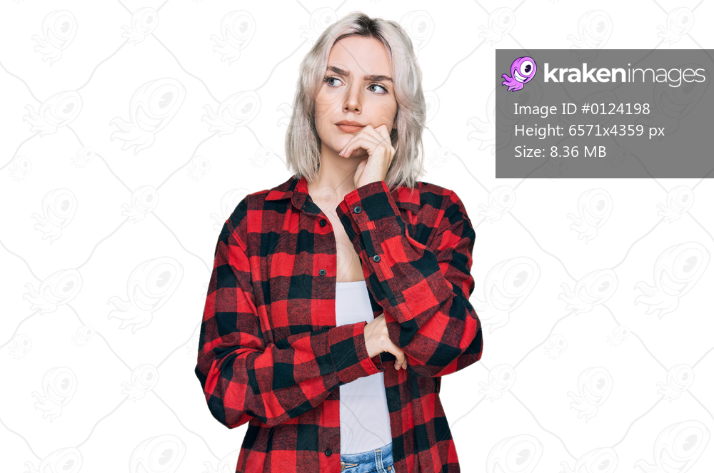 Young blonde girl wearing casual clothes serious face thinking about question with hand on chin, thoughtful about confusing idea