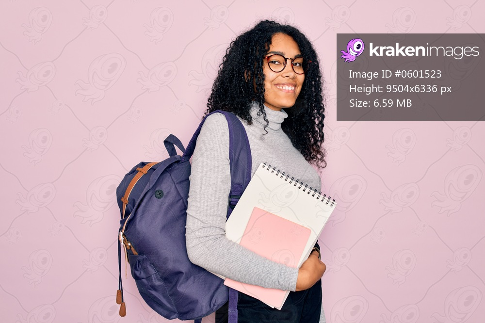 Young african american curly student woman wearing backpack and glasses holding book with a happy face standing and smiling with a confident smile showing teeth