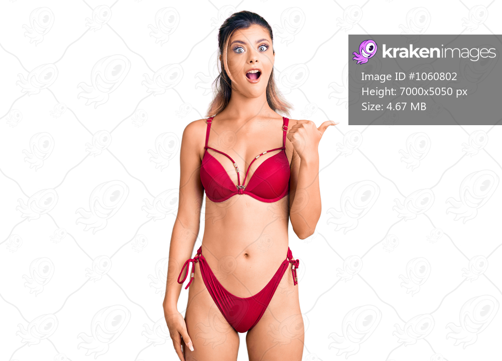 Young beautiful woman wearing bikini surprised pointing with hand finger to the side, open mouth amazed expression.
