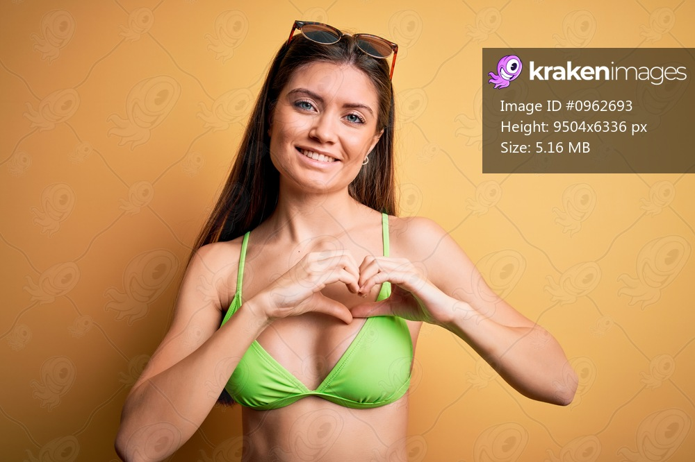 Young beautiful woman with blue eyes on vacation wearing bikini and sunglasses smiling in love showing heart symbol and shape with hands. Romantic concept.
