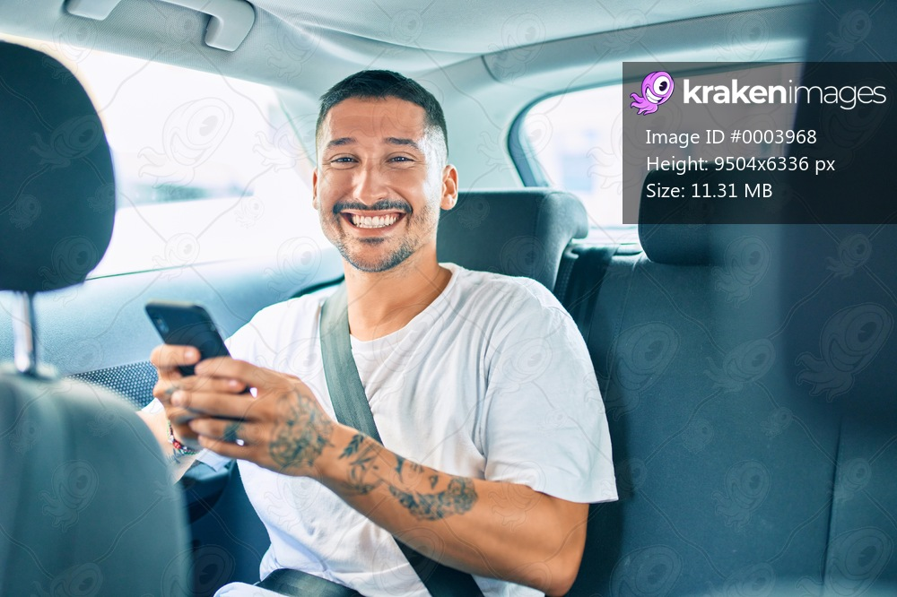 Young hispanic man smiling happy using smartphone sitting on the car.