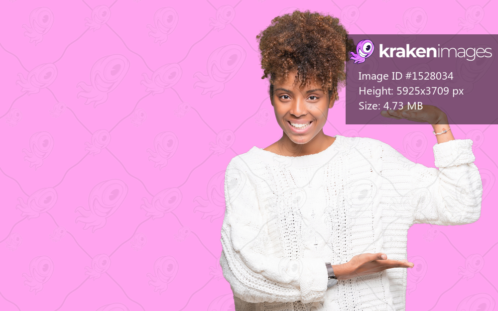 Beautiful young african american woman wearing winter sweater over isolated background gesturing with hands showing big and large size sign, measure symbol. Smiling looking at the camera. Measuring concept.