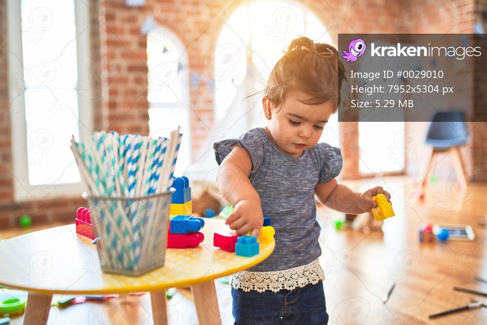 Beautiful toddler playing with building blocks toys at kindergarten