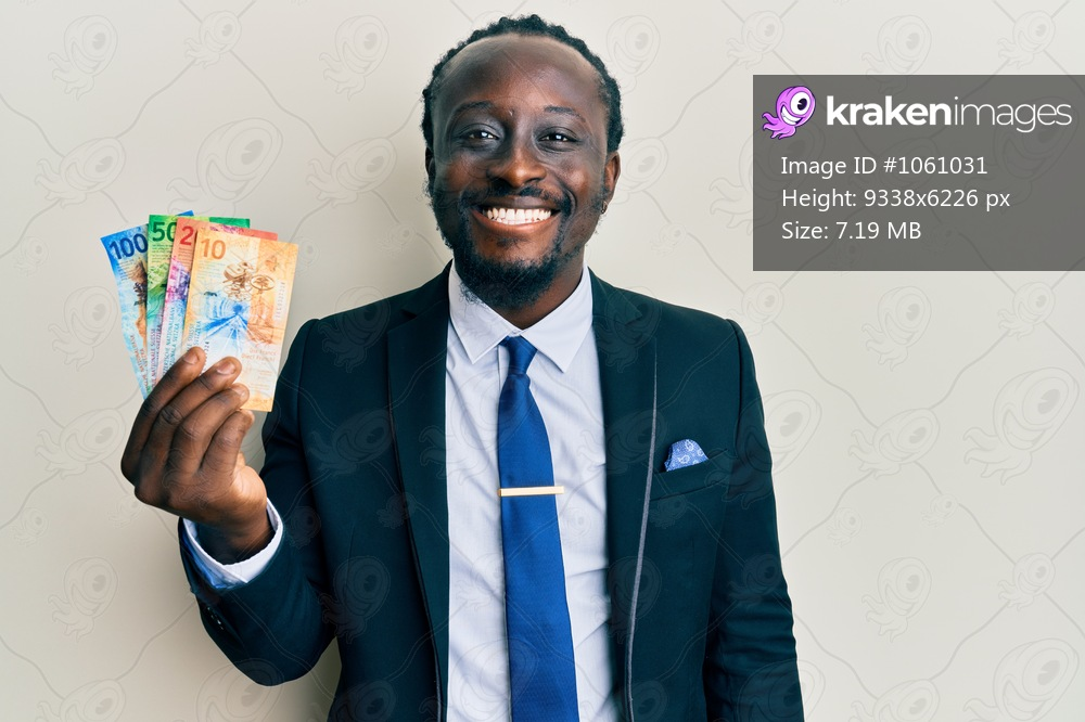 Handsome young black man wearing business suit holding franc swiss banknotes looking positive and happy standing and smiling with a confident smile showing teeth