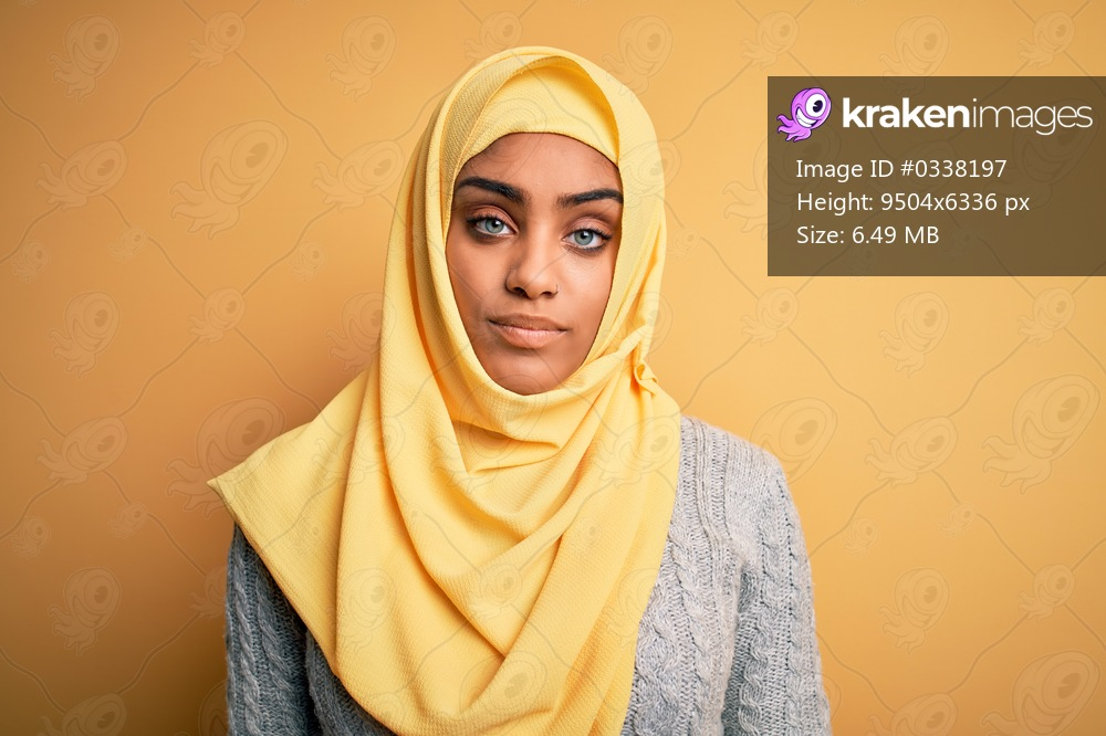 Young beautiful african american girl wearing muslim hijab over isolated yellow background looking sleepy and tired, exhausted for fatigue and hangover, lazy eyes in the morning.