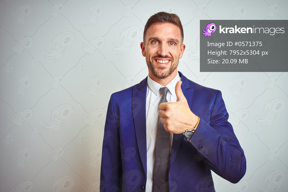 Young handsome business man over white isolated background doing happy thumbs up gesture with hand. Approving expression looking at the camera with showing success.