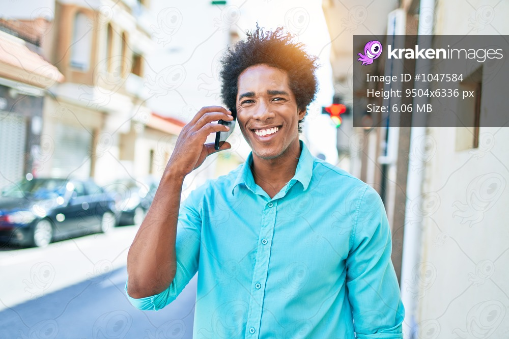 Young handsome african american man wearing casual clothes smiling happy. Standing with smile on face having conversation talking on the smartphone at town street.