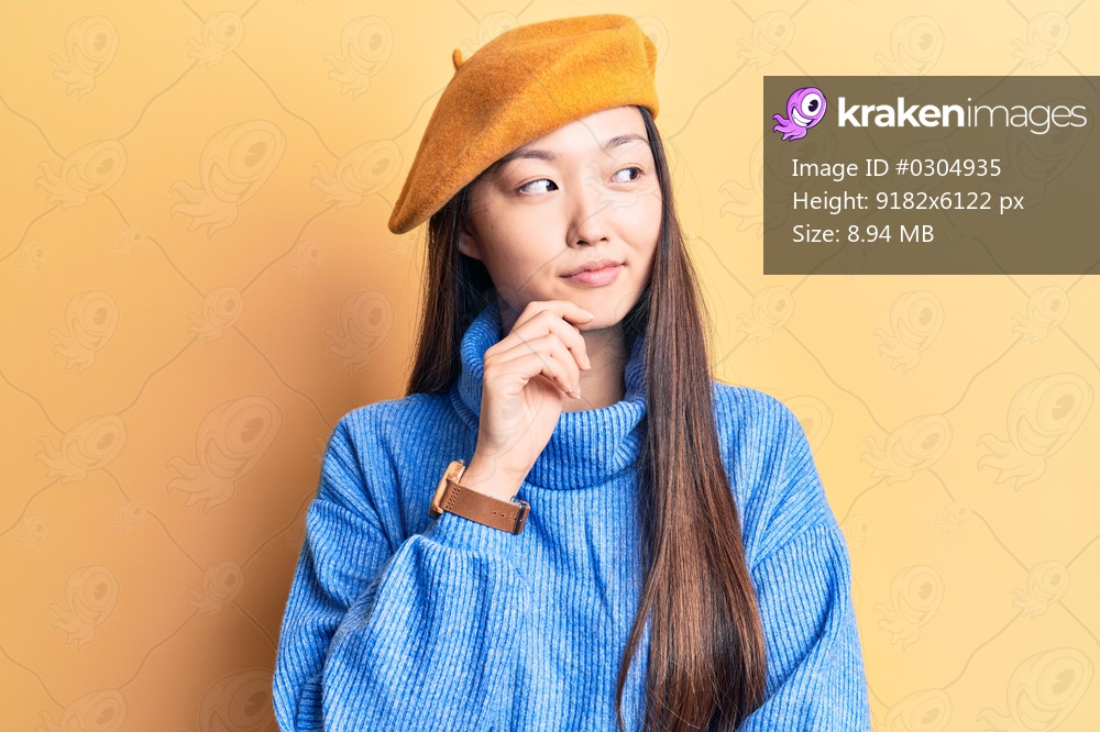Young beautiful chinese woman wearing turtleneck sweater and french beret thinking concentrated about doubt with finger on chin and looking up wondering