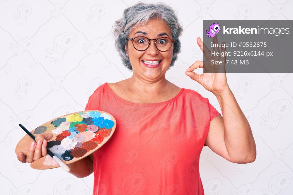Senior hispanic grey- haired woman holding paintbrush and palette doing ok sign with fingers, smiling friendly gesturing excellent symbol