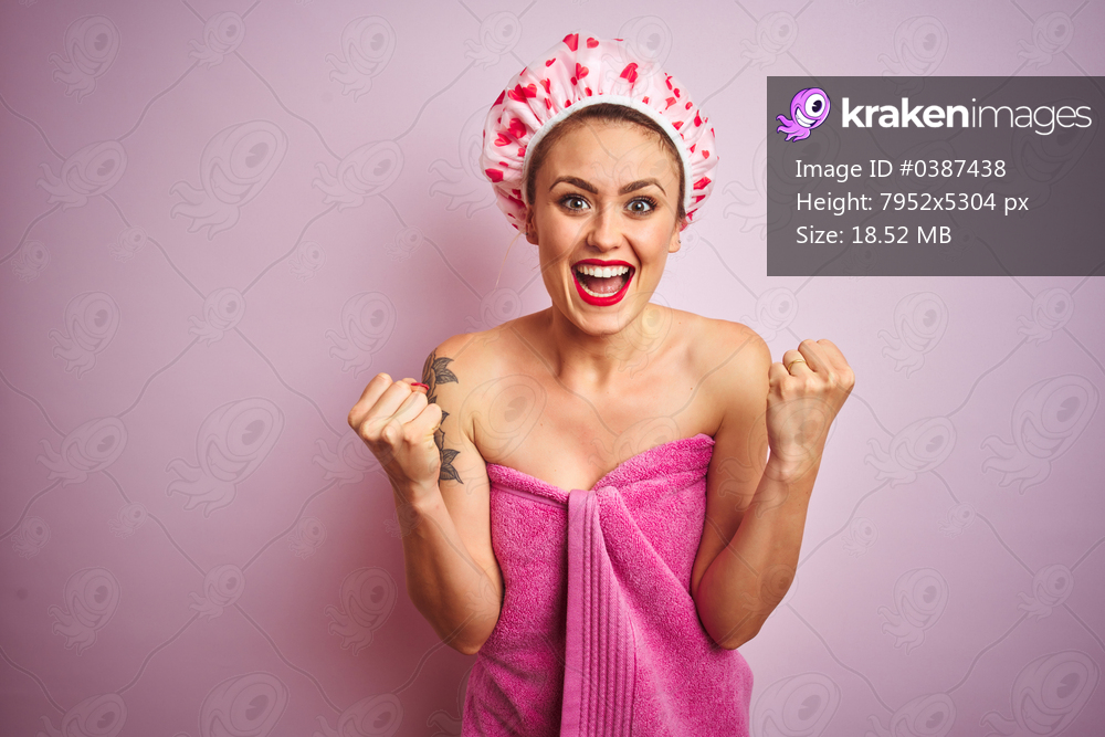 Young beautiful woman wearing towel and bath hat after shower over pink isolated background celebrating surprised and amazed for success with arms raised and open eyes. Winner concept.