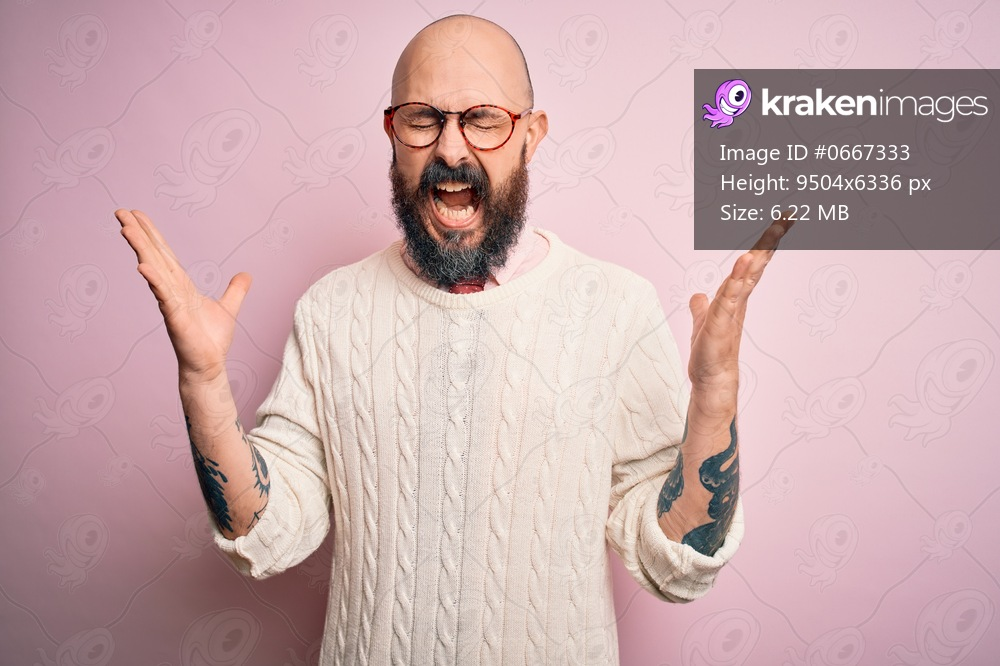 Handsome bald man with beard and tattoo wearing glasses and sweater over pink background celebrating mad and crazy for success with arms raised and closed eyes screaming excited. Winner concept