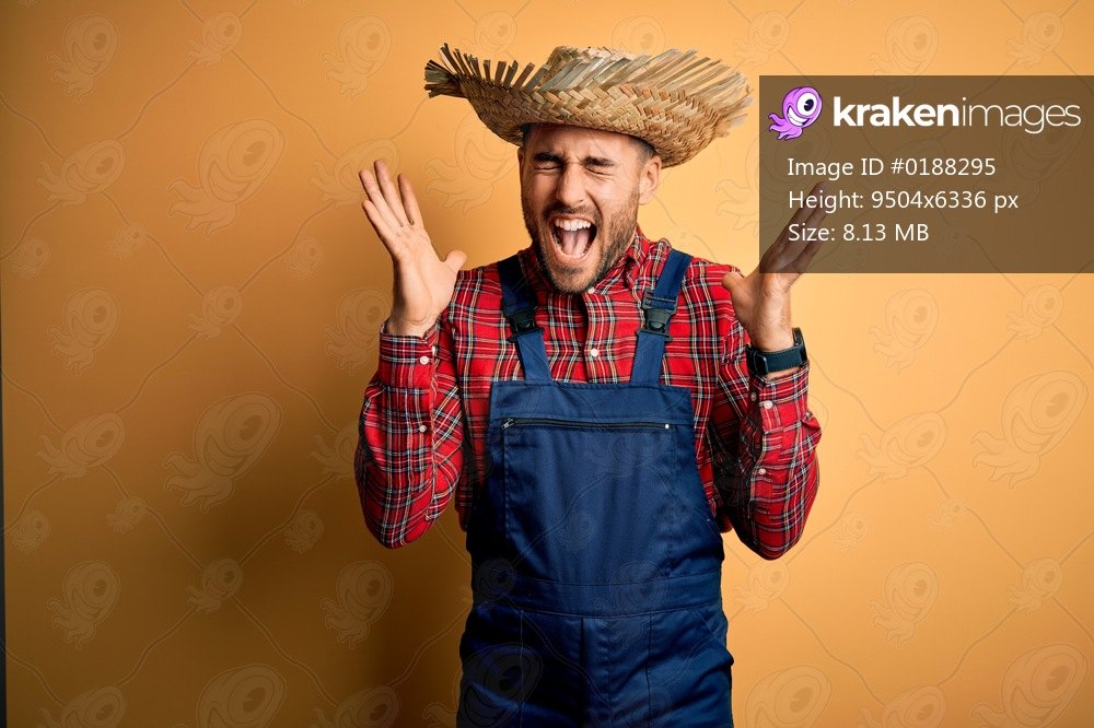 Young rural farmer man wearing bib overall and countryside hat over yellow background celebrating mad and crazy for success with arms raised and closed eyes screaming excited. Winner concept