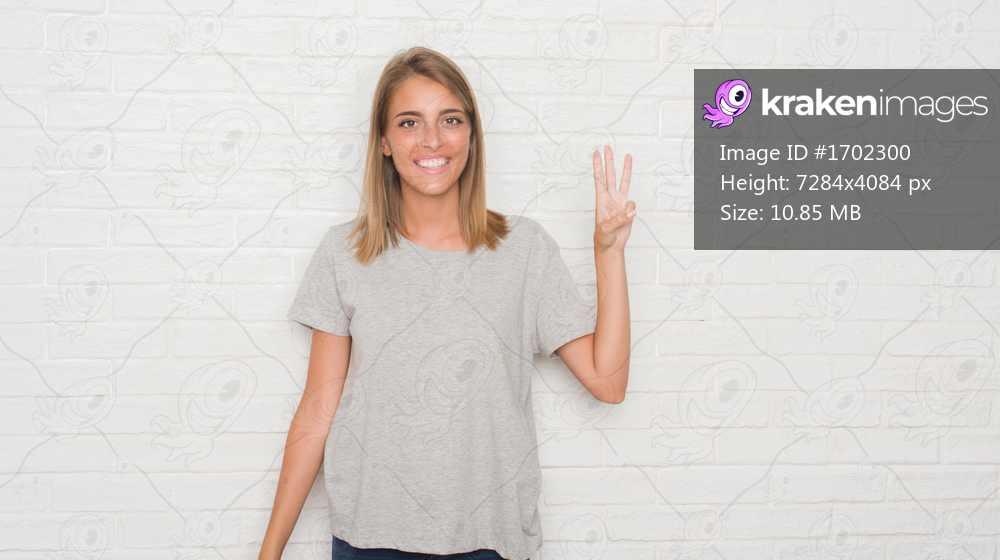 Beautiful young woman over white brick wall showing and pointing up with fingers number three while smiling confident and happy.