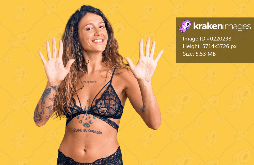 Young hispanic woman with tattoo wearing lingerie showing and pointing up with fingers number ten while smiling confident and happy.