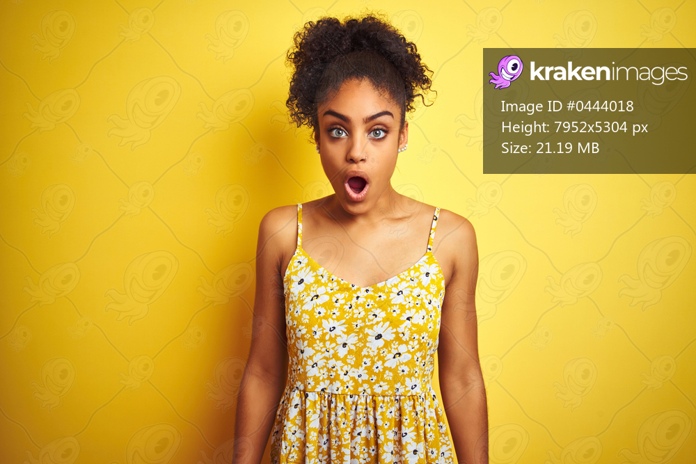 African american woman wearing casual floral dress standing over isolated yellow background afraid and shocked with surprise and amazed expression, fear and excited face.