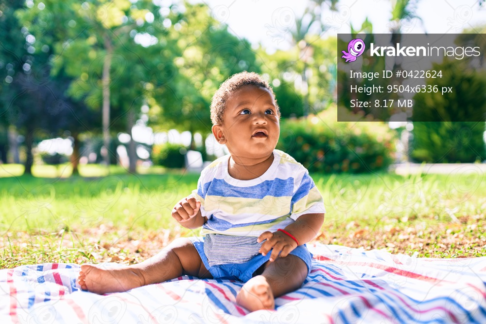 Adorable african american toddler sitting on the grass at the park.