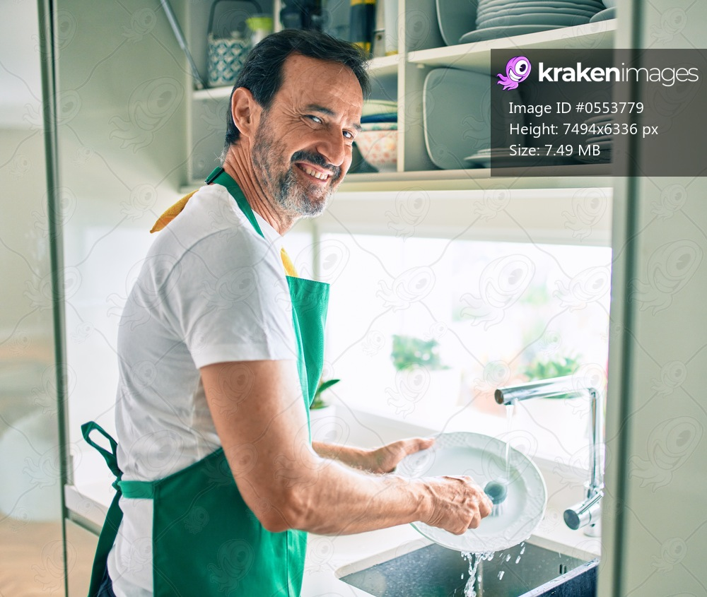 Middle age man with beard smiling happy washing dishes at home
