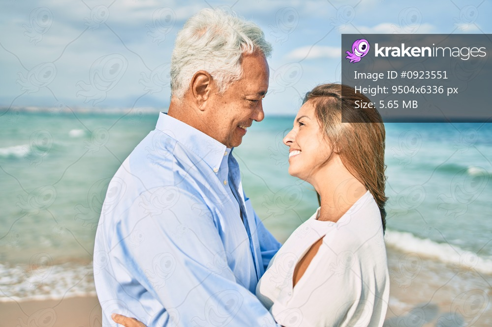 Middle age hispanic couple smiling happy and hugging walking at the beach
