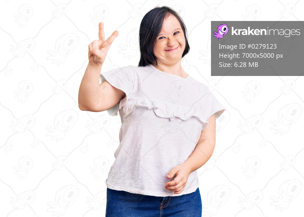 Brunette woman with down syndrome wearing casual white tshirt smiling with happy face winking at the camera doing victory sign with fingers. number two.