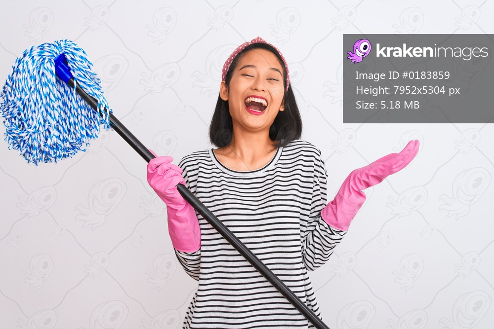 Young chinese cleaner woman wearing gloves holding mop over isolated white background very happy and excited, winner expression celebrating victory screaming with big smile and raised hands
