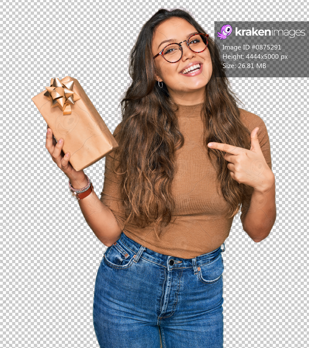 Young hispanic girl holding gift smiling happy pointing with hand and finger