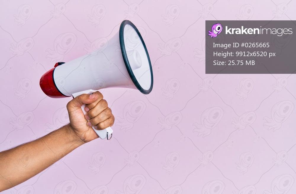 Hand of hispanic man holding megaphone over isolated pink background.