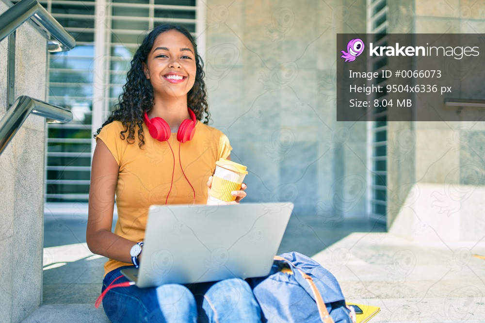 Young african american student girl using laptop sitting on stairs at university.
