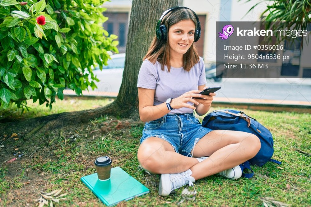 Young middle east student girl smiling happy using headphones and smartphone at the university campus.