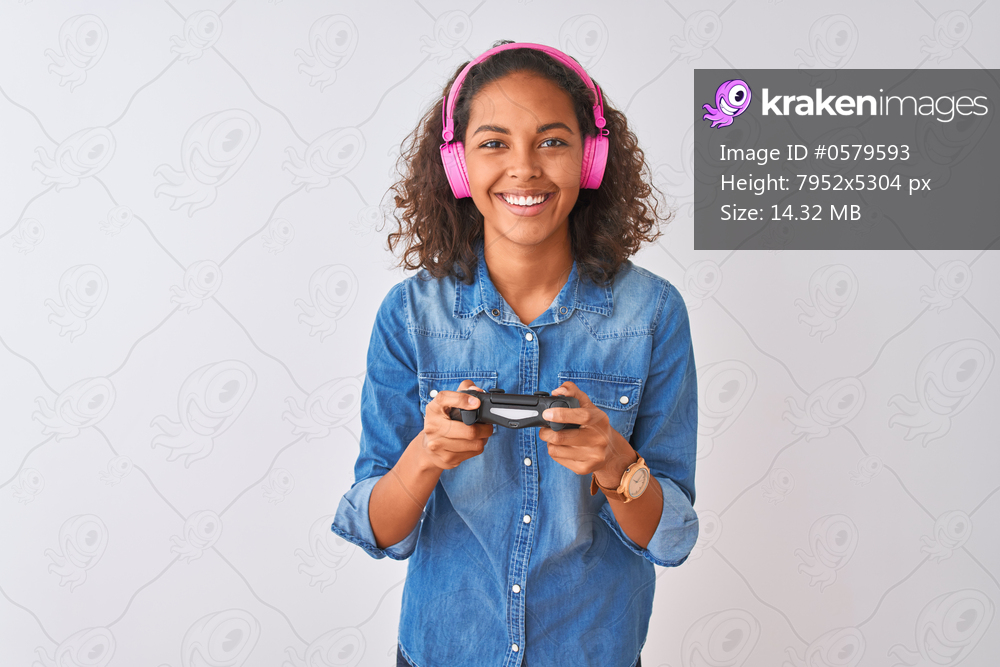 Brazilian gamer woman playing video game using headphones over isolated white background with a happy face standing and smiling with a confident smile showing teeth