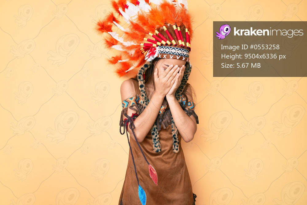 Young beautiful latin girl wearing indian costume with sad expression covering face with hands while crying. depression concept.