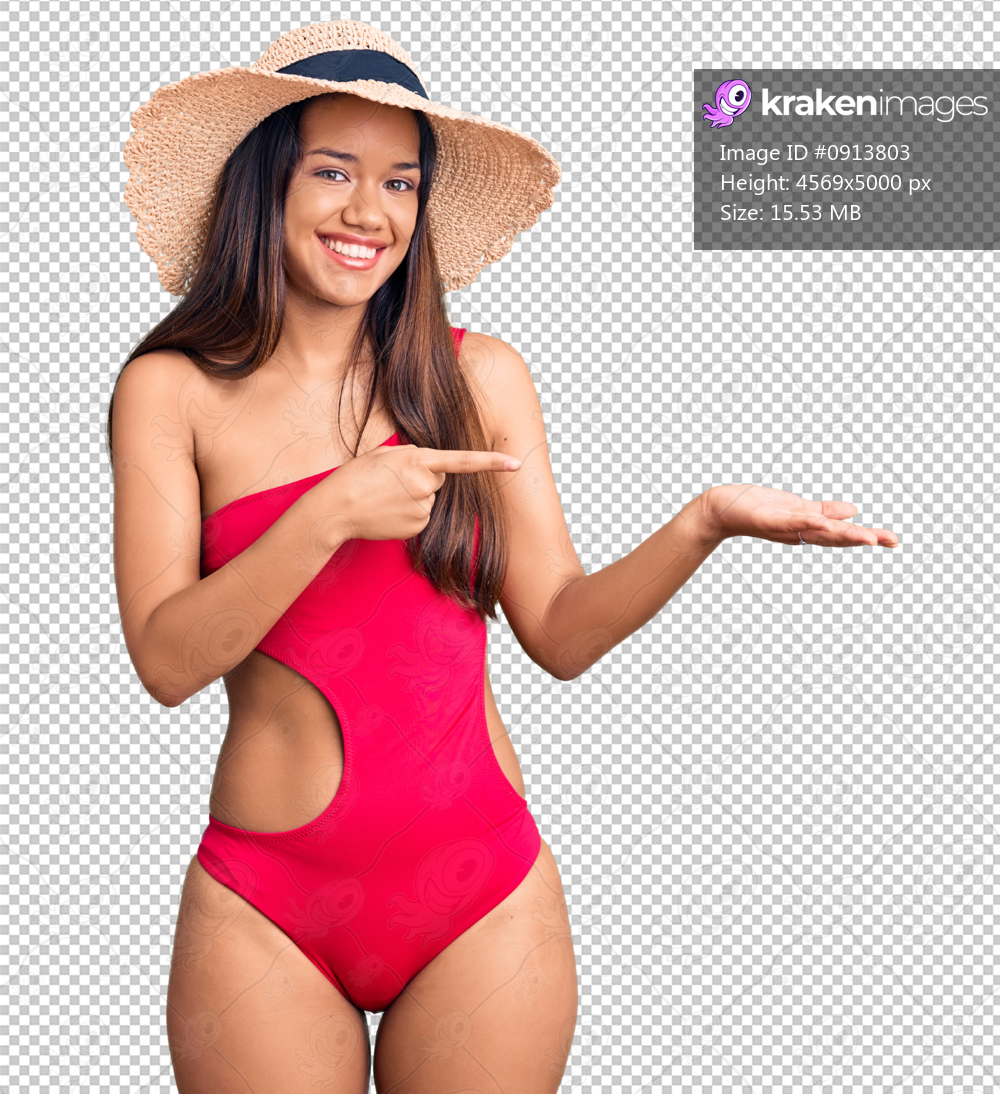 Young beautiful latin girl wearing swimwear and summer hat amazed and smiling to the camera while presenting with hand and pointing with finger.
