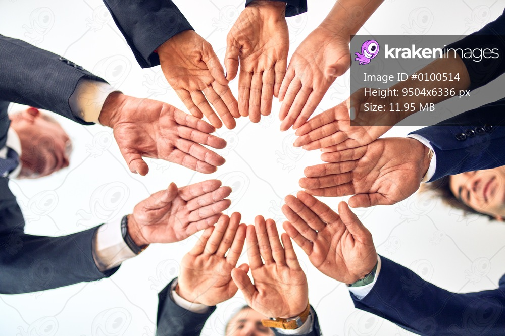 Group of business workers smiling happy and confident. Standing on a circle with smile on face doing symbol with hands together at the office.