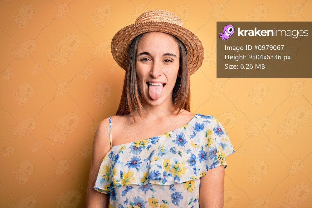 Young beautiful woman wearing casual t-shirt and summer hat over isolated yellow background sticking tongue out happy with funny expression. Emotion concept.