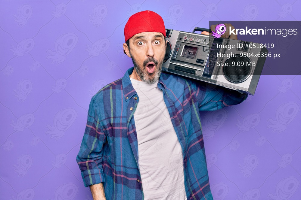 Middle age man wearing cap listening vintage boombox over isolated purple background scared and amazed with open mouth for surprise, disbelief face