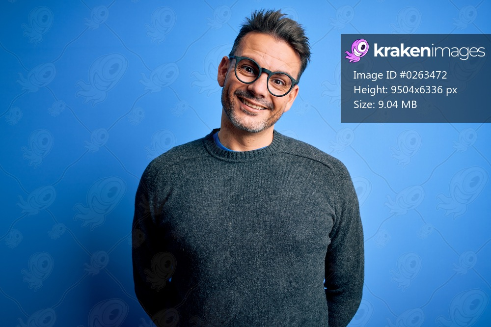 Young handsome man wearing casual sweater and glasses standing over blue background with a happy and cool smile on face. Lucky person.