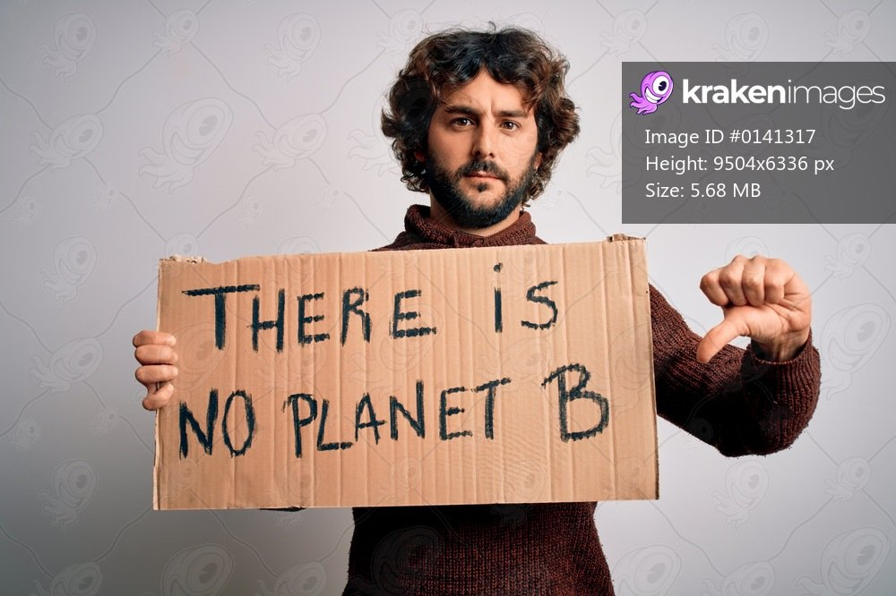 Young handsome man with beard asking for environment holding banner with earth message with angry face, negative sign showing dislike with thumbs down, rejection concept