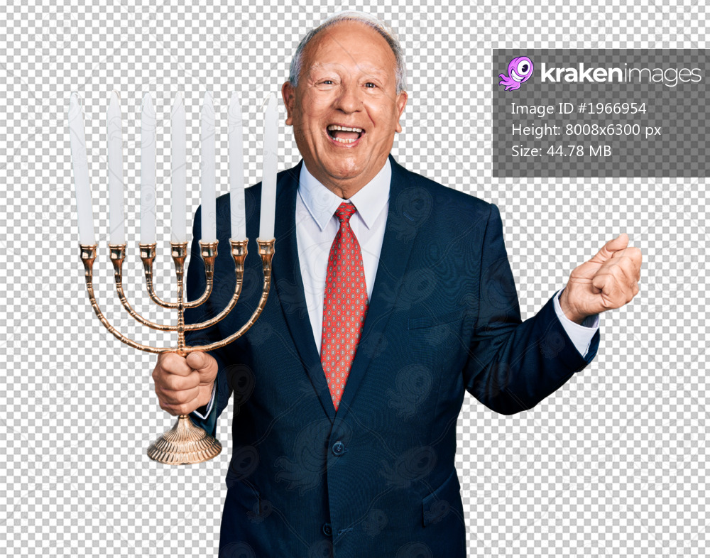 Senior business man with grey hair holding menorah hanukkah jewish candle screaming proud, celebrating victory and success very excited with raised arm