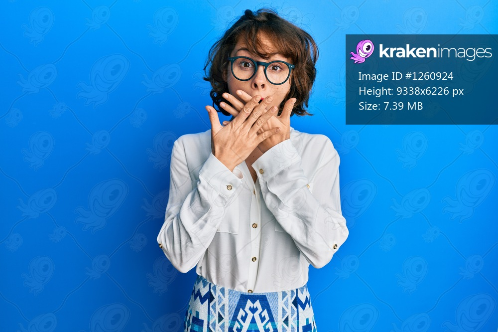 Young brunette woman wearing casual clothes and glasses shocked covering mouth with hands for mistake. secret concept.